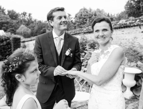 Photo d'un marié passant l'alliance au doigt de sa femme